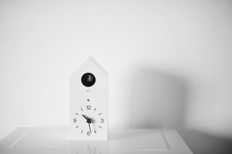 Clock on table against white background