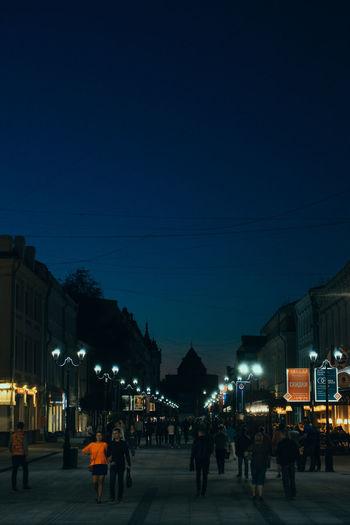 People walking on illuminated street amidst buildings at night