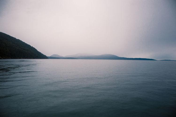 Scenic view of sea against foggy, raining sky