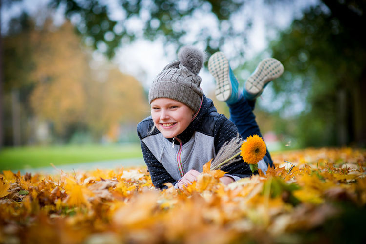 Smiling boy with autumn leaves