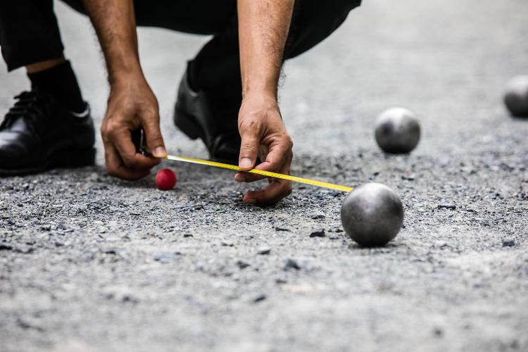 Low section of man measuring metallic sphere on land