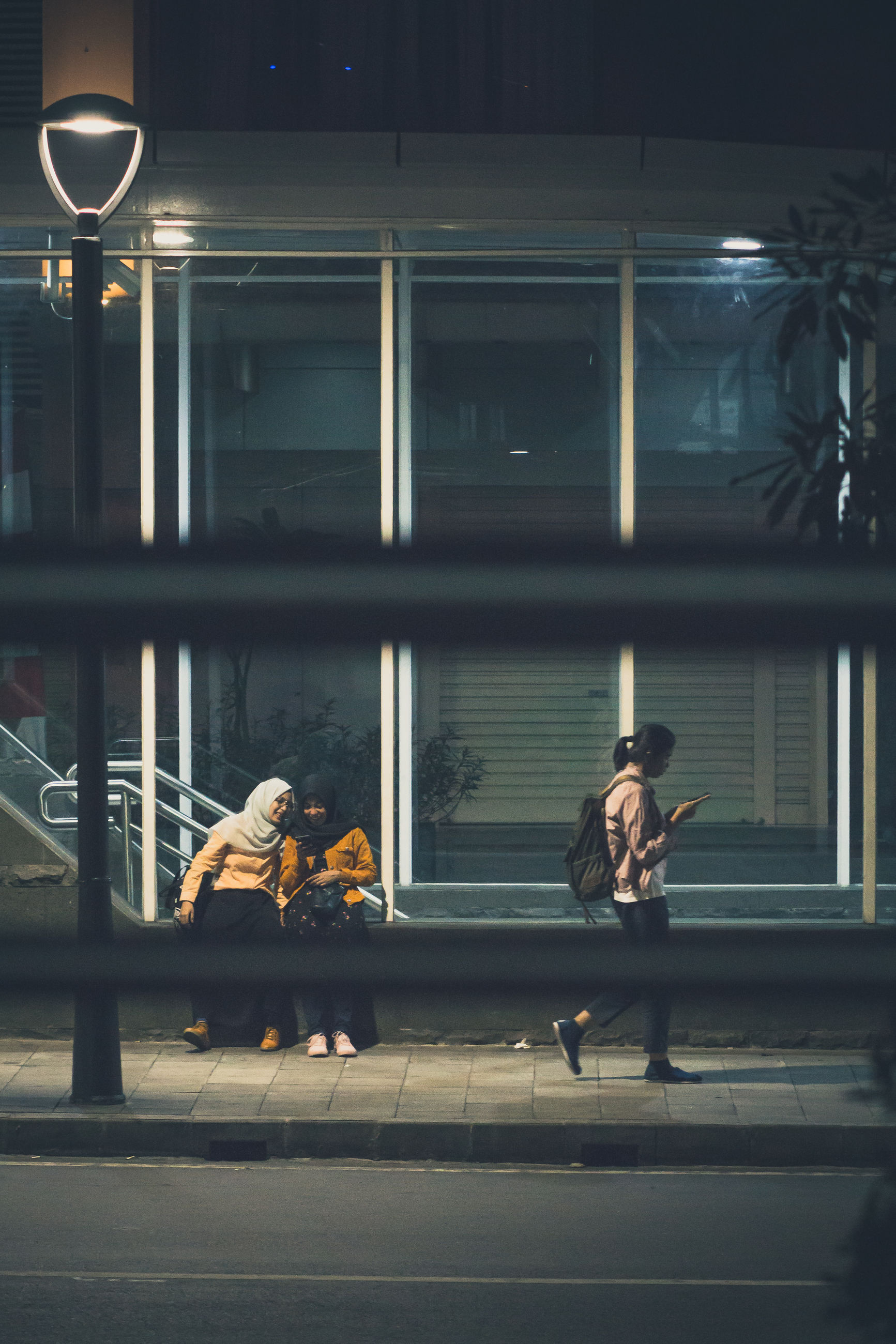 city, architecture, street, night, real people, group of people, women, built structure, illuminated, building exterior, people, lifestyles, window, transportation, full length, leisure activity, glass - material, outdoors, men, adult