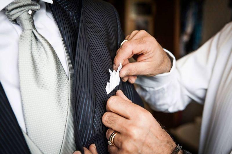Cropped hand of man adjusting handkerchief of friend