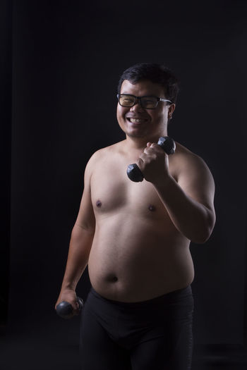 Shirtless Overweight Man Holding Dumbbells While Standing Against Black Background