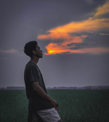 Man kneeling on field against sky during sunset