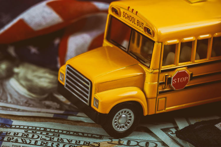 Close up school busses, american dollars cash money and Usa Flag. American Flag Business Dollar Sign HUNDRED School Bus Stop School Buses America American Culture Car Cash Close-up Dollar Finance Finance And Economy Focus On Foreground Indoors  Mode Of Transportation Money No People School School Bus Transportation Wealth Yellow