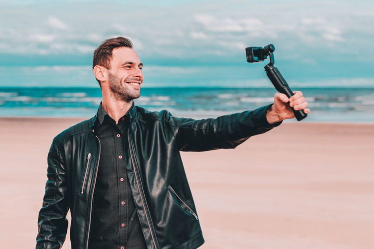 Smiling young man filming with video camera at beach