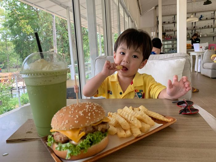 Food And Drink Food Table Fast Food Childhood Ready-to-eat Unhealthy Eating Child Burger One Person Sandwich Prepared Potato Hamburger French Fries Portrait Freshness Real People Indoors  Front View Fried Glass Temptation Snack