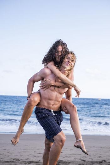 Full Length Of Man Piggybacking Girlfriend At Beach