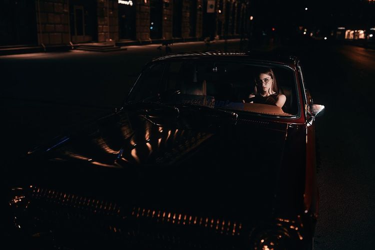 Portrait of young woman sitting in car on road at night