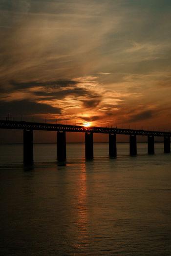Bridge over calm sea at sunset