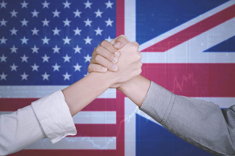 Digital Composite Image Of Business People Giving Handshake Against Flags