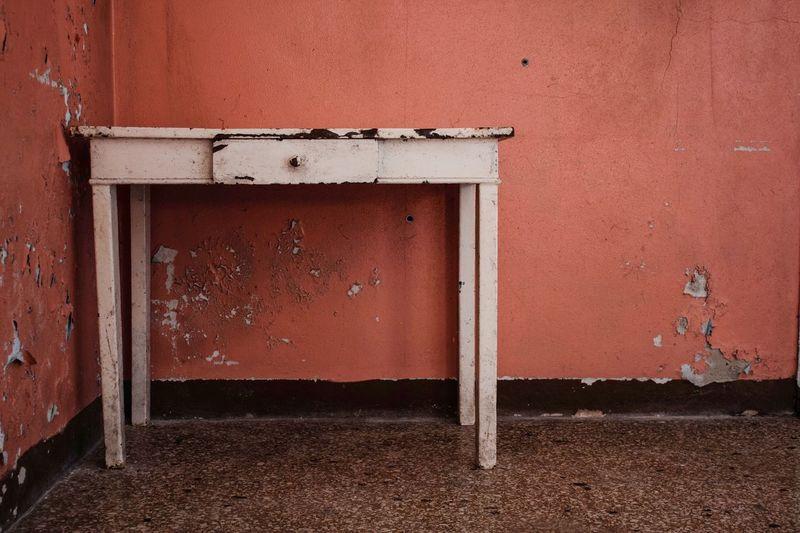 Old Rusty Metal Table Against Orange Wall In Room