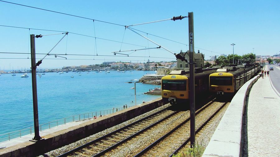 Trains Moving On Railroad Track By Sea Against Clear Blue Sky