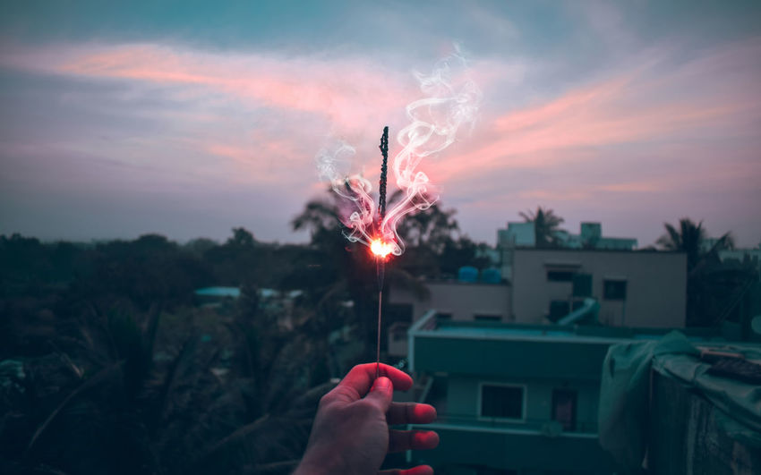 Architecture Building Exterior Built Structure Burning Cloud - Sky Finger Fire Firework Firework - Man Made Object Firework Display Hand Holding Human Body Part Human Hand Nature One Person Outdoors Real People Sky Smoke - Physical Structure Sparkler Sunset Unrecognizable Person