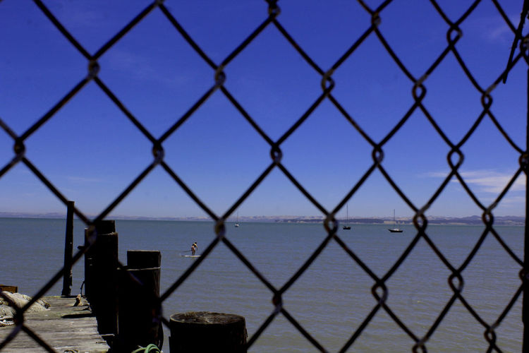 Beauty In Nature Chainlink Fence Clear Sky Close-up Day Focus On Foreground Frame Horizon Over Water Metal Nature No People Outdoors Protection Safety Sea Security Sky Water