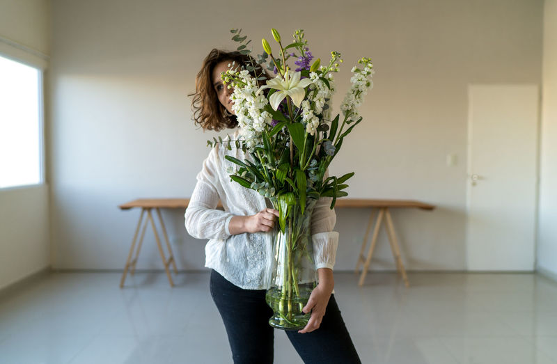 Woman holding flower vase against wall at home