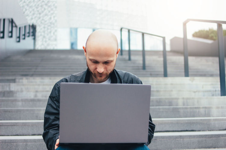 Businessman using laptop sitting on staircase