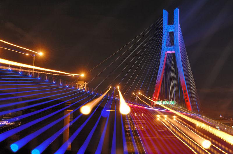 Light trails on bridge against sky at night