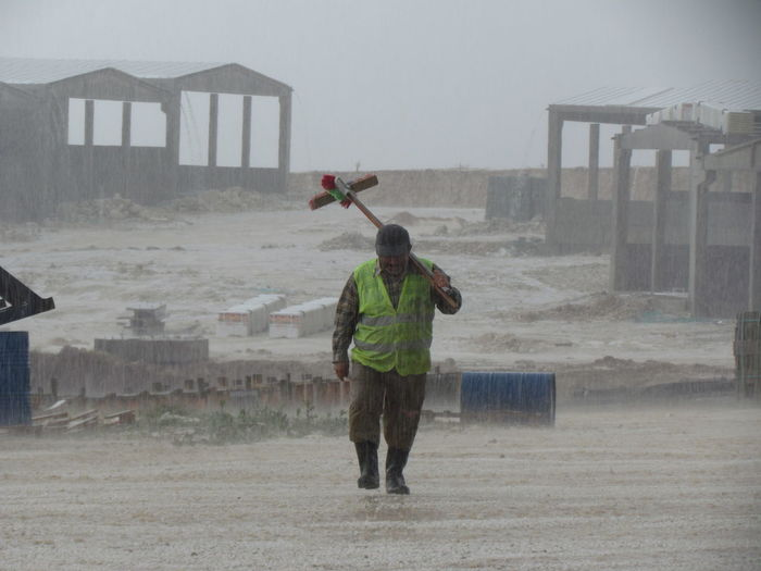 Worker walking by construction site on rainy day