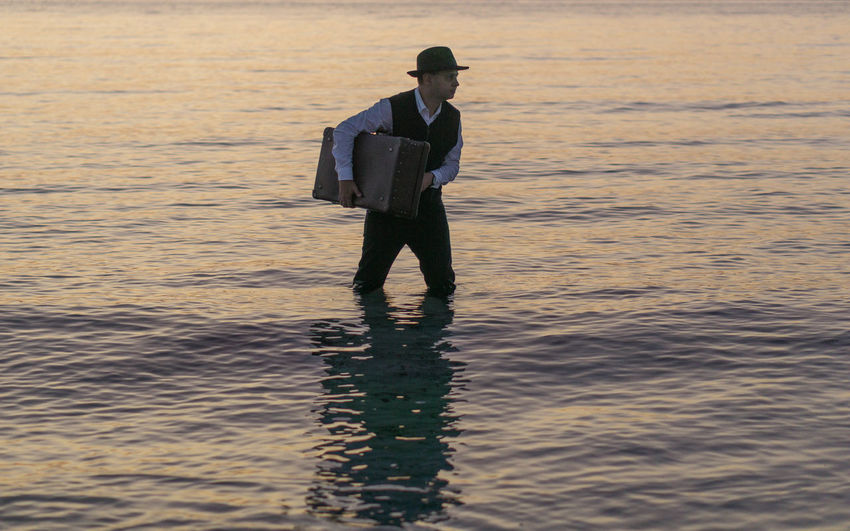 Man with briefcase wading in sea