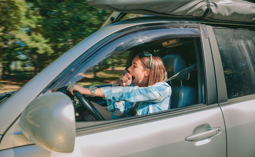 Young woman yawning while traveling in car