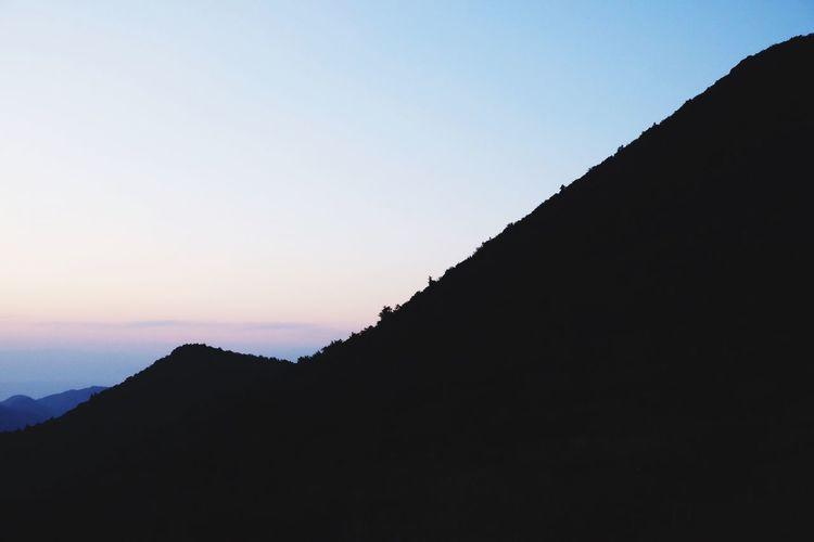 Silhouette mountain range against sky during sunset
