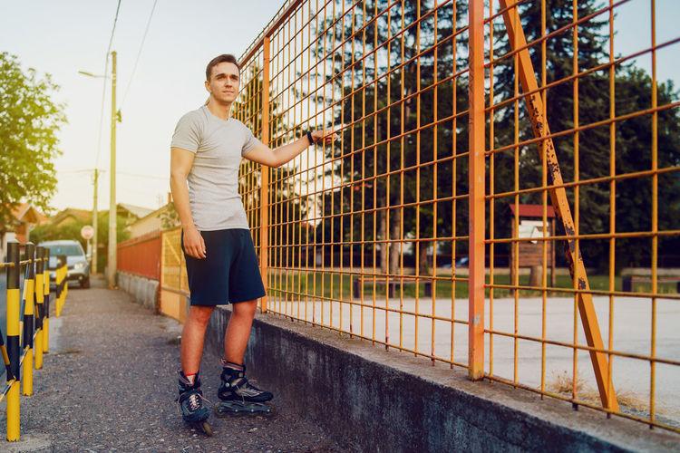 Full length of man roller skating on footpath by metal grate