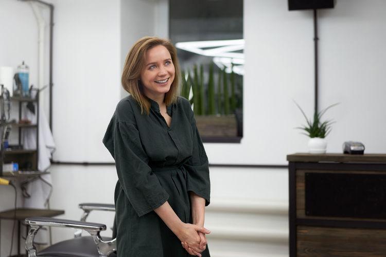 Beautiful woman hairdresser in modern barbershop