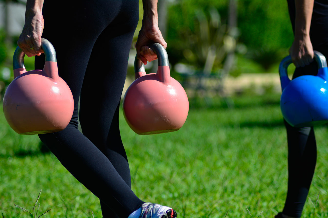 Low section of men carrying kettlebell on grass