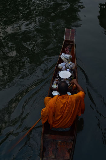 Rear view of monk sitting on boat in lake