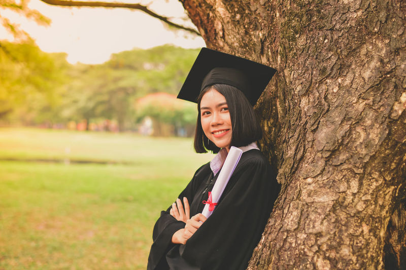 Portrait Of Young Woman In Graduation Gown Holding Certificate While Standing By Tree At Park