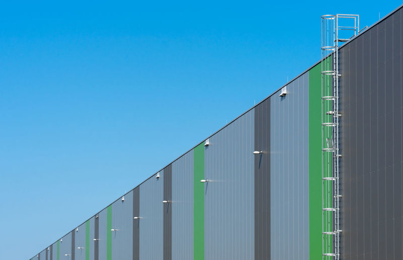 Low angle view of warehouse building against clear blue sky