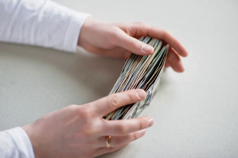 Cropped hands holding paper currencies at table