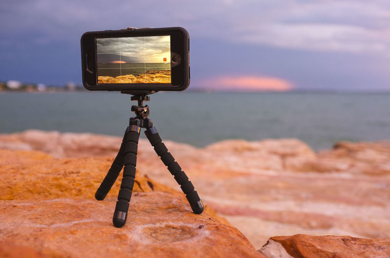 Mobile phone on a mini tripod recording a time-lapse at East Point in Darwin, Northern Territory, Australia. Water Photography Themes Technology Sea Communication Tripod Camera - Photographic Equipment Sunset Horizon Over Water Horizon Photographic Equipment No People Nature Beach Scenics - Nature IPhoneography Mobile Photography Mobile Video Memories