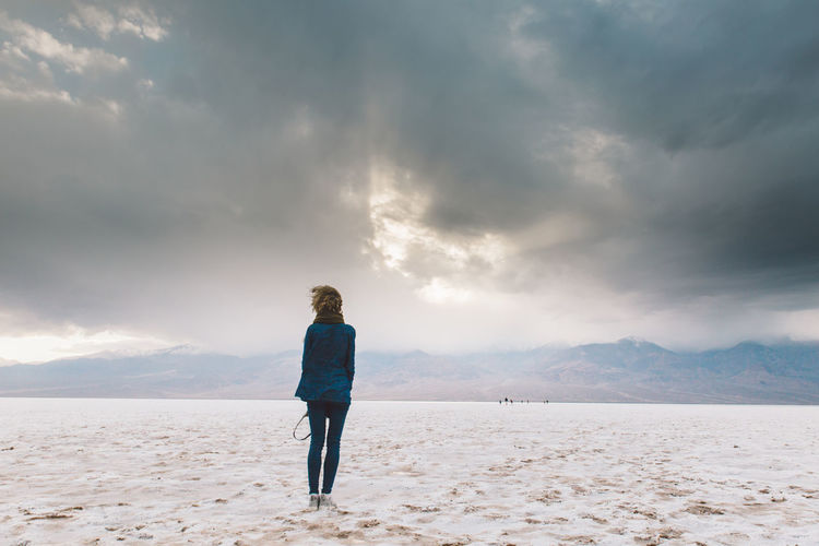Rear view of woman standing on sand against sky