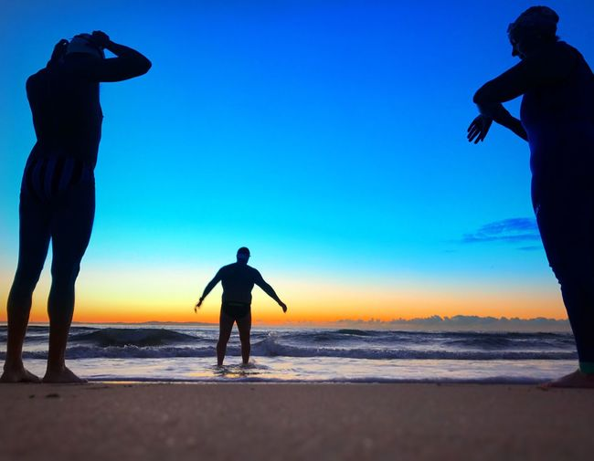 Silhouette men standing on beach against clear sky