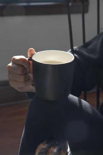 woman holds a mug of coffee Cup Hand Human Hand Mug Coffee One Person Drink Refreshment Food And Drink Holding Coffee - Drink Coffee Cup Finger Dark Background Contrast Black Clothes Holding Coffee Mug Coffee And Cream Latte Morning
