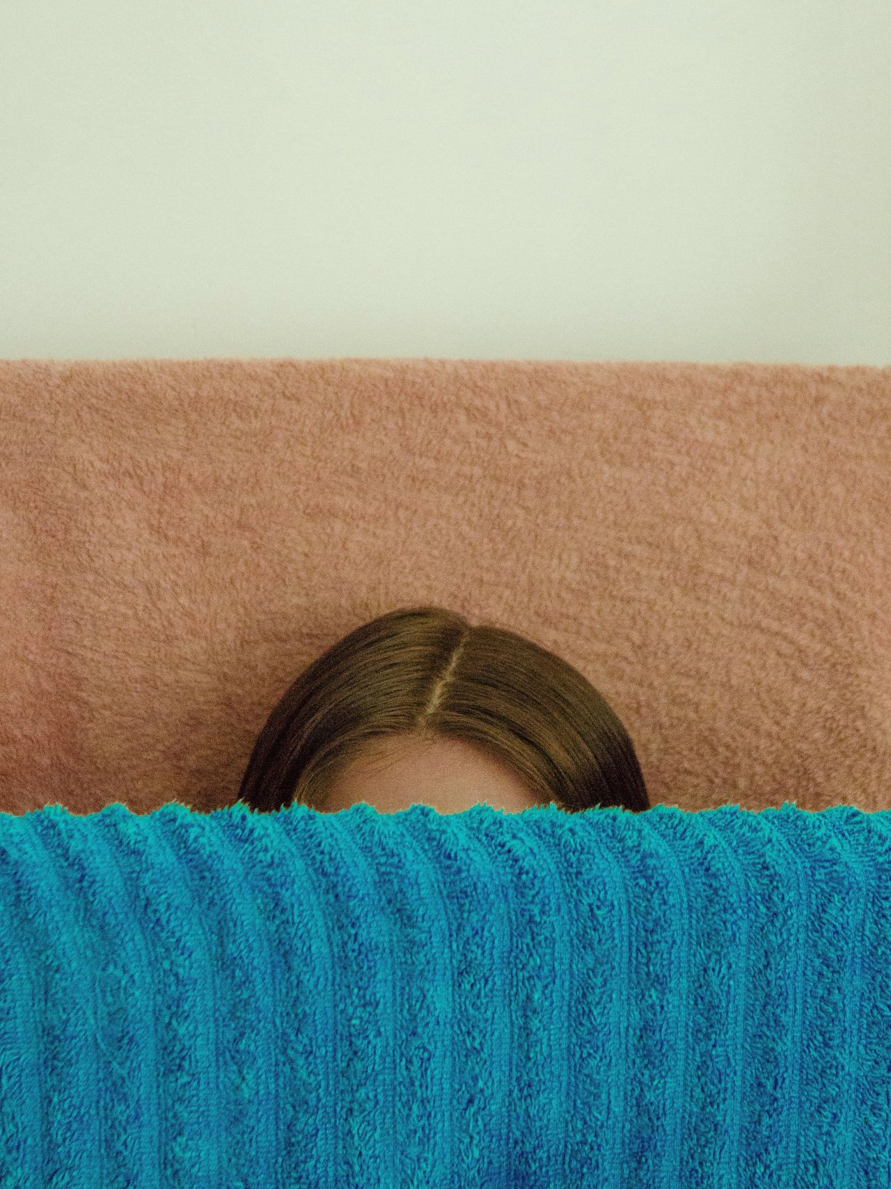 Cropped image of woman with fabric against wall