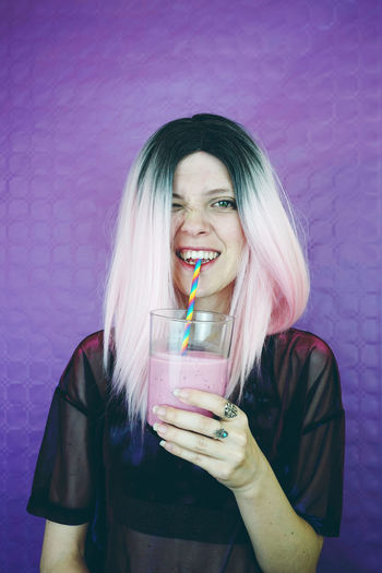 Portrait of young woman drinking smoothie while standing against wall