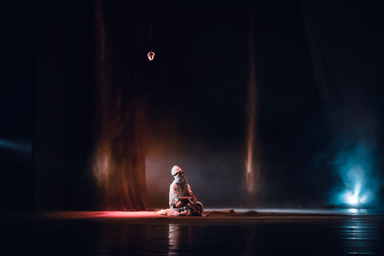 Blurred motion of man sitting on illuminated stage at night