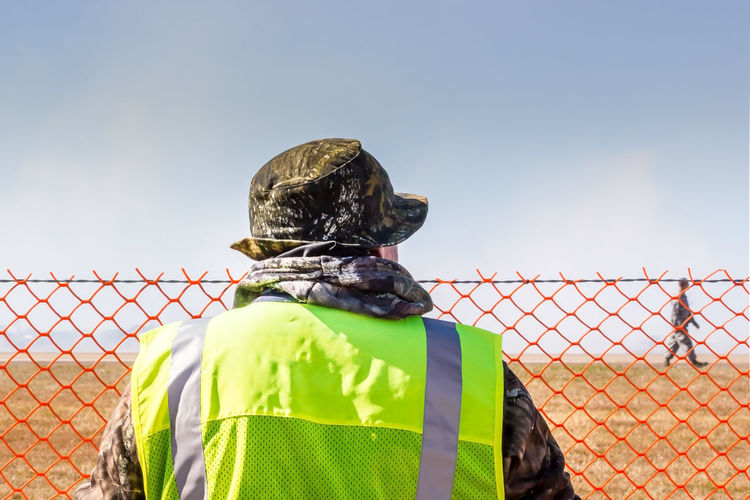 Rear view of soldier wearing uniform while standing by fence against sky