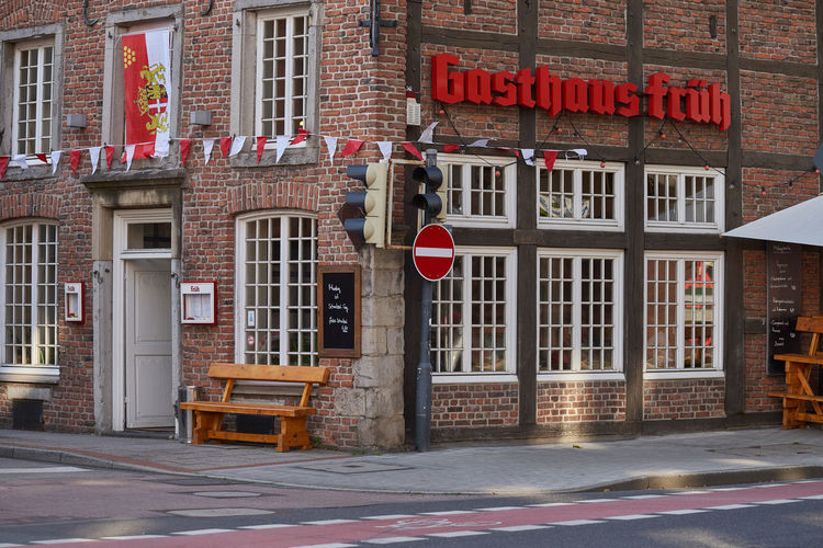 NEUSS, GERMANY - AUGUST 08, 2016: Historic building hosts a traditional tavern at a street corner Advertising Business Finance And Industry City Life City Street Commercial Dock Culture Downtown Historic Historic Buildings Urban History Medieval Neuss, Germany Pedestrants Shopping
