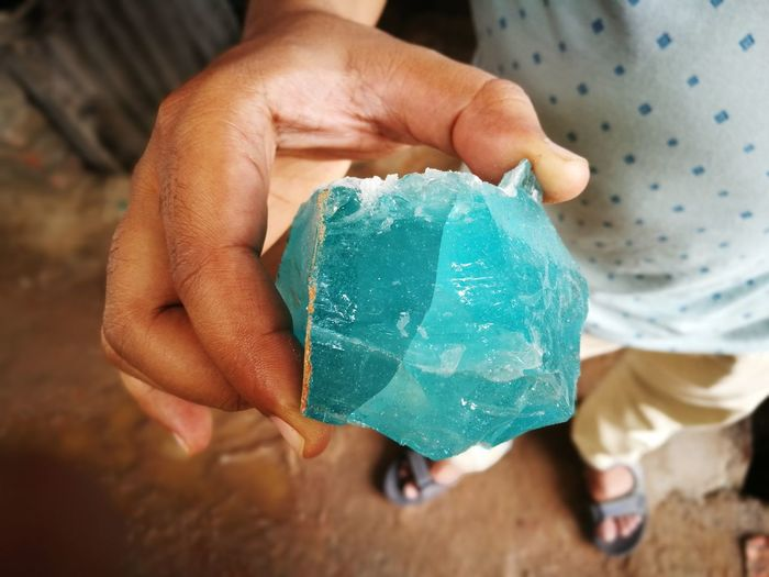 Low Section Of Man Holding Blue Mineral