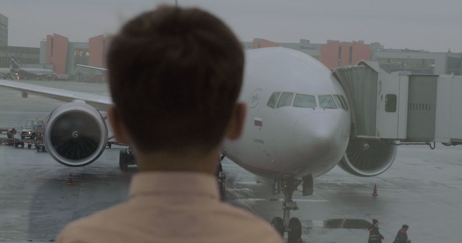 Rear view of man and woman at airplane
