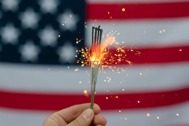 Cropped hand of person holding illuminated sparklers against american flag