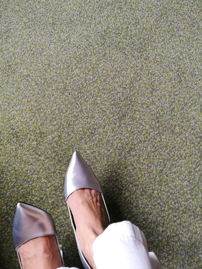 Low section of woman wearing shoes on floor