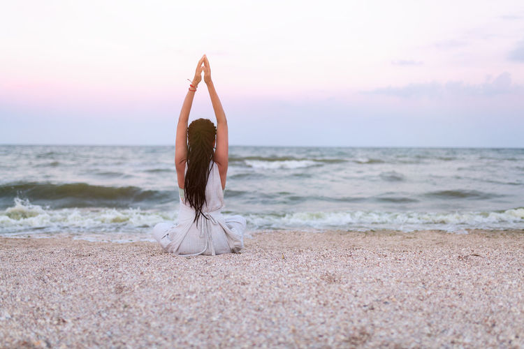 Woman doing yoga at beach against sky during sunset