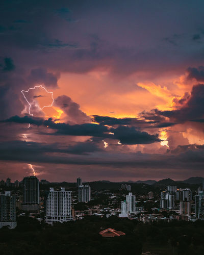 Scenic view of city against dramatic sky during sunset