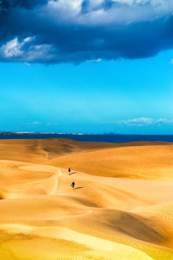 Scenic view of dunes at maspalomas with two people